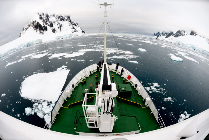 Ship Pushing Through Ice in the Lemaire Channel in Antarctica